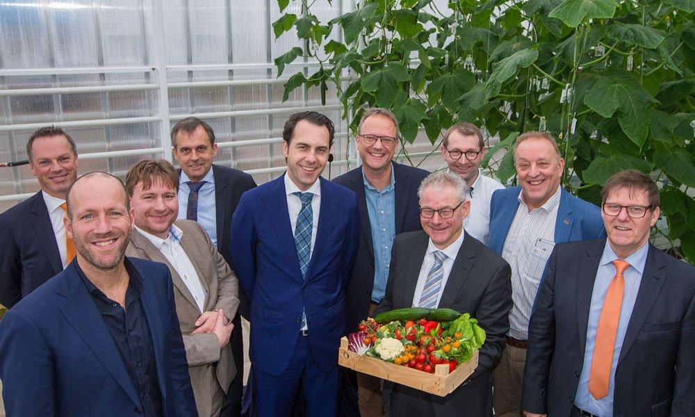 Staatssecretaris Martijn van Dam samen met de projectpartners bij de opening van de Winterlichtkas in Wageningen.