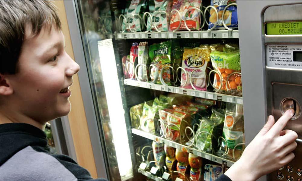 Jongen voor snoepautomaat