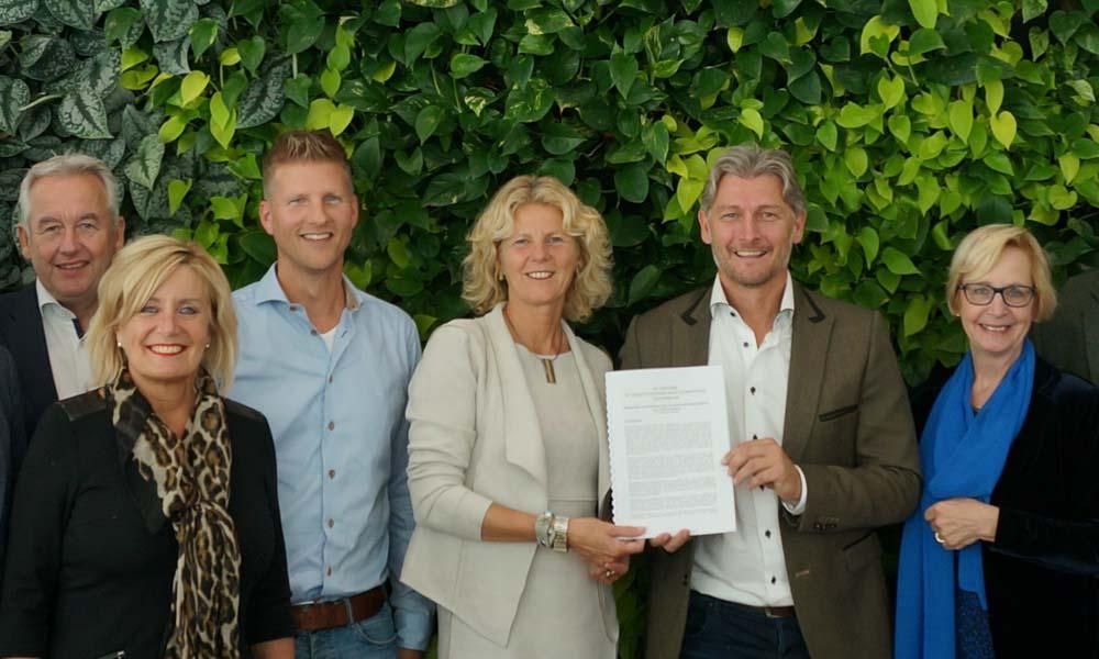 Jacco Vooijs (tweede van rechts) biedt de visie glastuinbouw van LTO Glaskracht aan burgemeester Agnes van Ardenne – van der Hoeven aan.